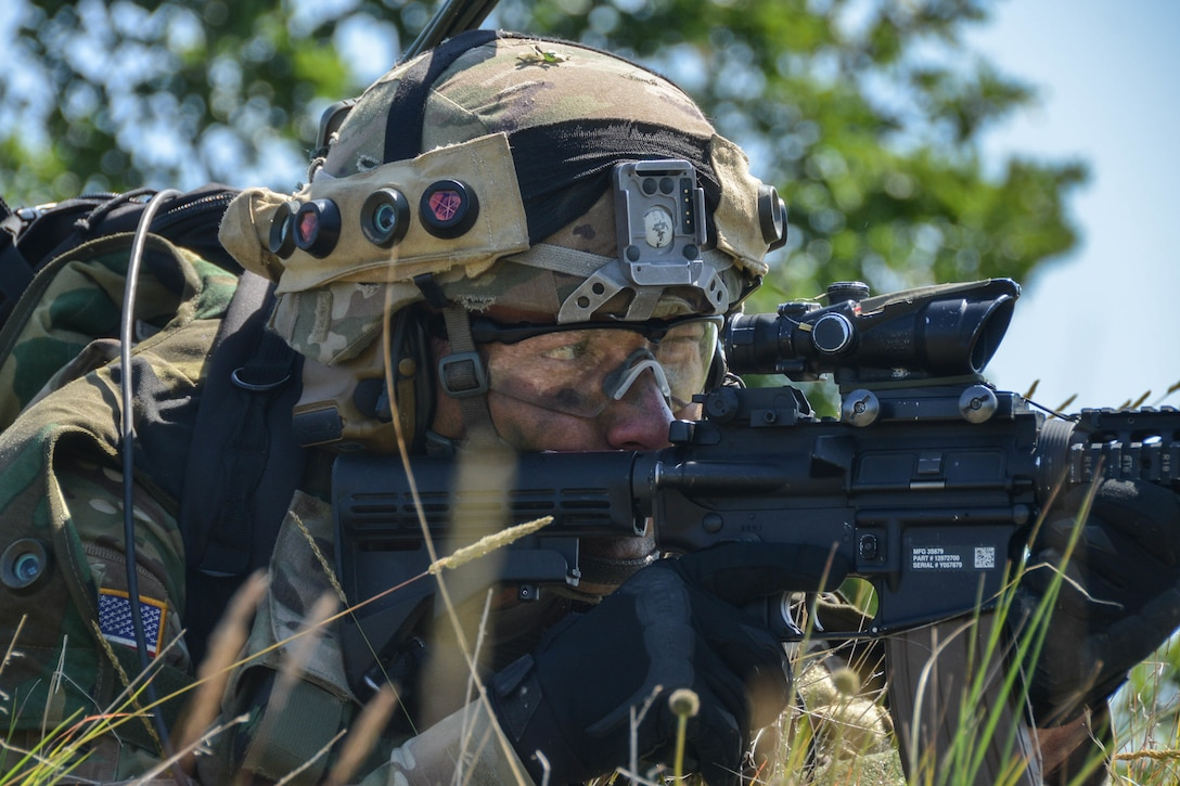 A soldier in camouflage aims a rifle from the ground.
