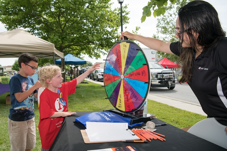 Children spin a wheel for a chance to win prizes from Sky Zone trampoline park located in  Newark during the Hurricane Block Party June 6, 2019, at the Eagle Heights family housing on Dover Air Force Base, Del. This year's block party offered attendees the chance to meet with four military agencies and 13 local vendors. (U.S. Air Force Photo by Mauricio Campino)
