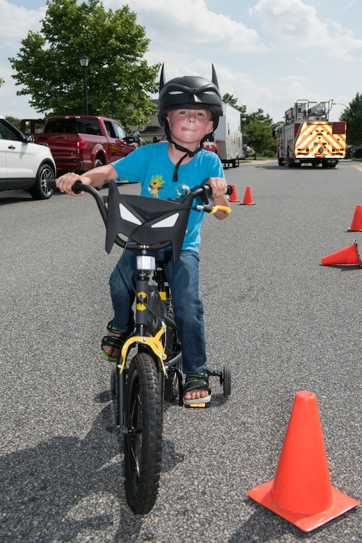 Nicholas Roof Jr. rides his bicycle through a safety course at the Hurricane Block Party June 6, 2019, at the Eagle Heights family housing on Dover Air Force Base, Del.  The course was set up by the 436th Security Forces squadron to show children how to maneuver around obstacles, test their brakes and to inspect the fit of their helmets. (U.S. Air Force Photo by Mauricio Campino)