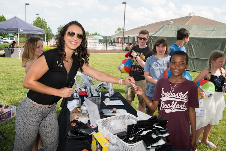 Jessica Ekin, director of marketing and business development for the Dover Mall and Dover commons, hands out raffle prizes to attendees of the Hurricane Block Party June 6, 2019, at the Eagle Heights family housing on Dover Air Force Base, Del. In addition to free food donated and prepared by the Eagle Heights housing staff,  door prizes and raffles were also donated by the various vendors in attendance. (U.S. Air Force Photo by Mauricio Campino)