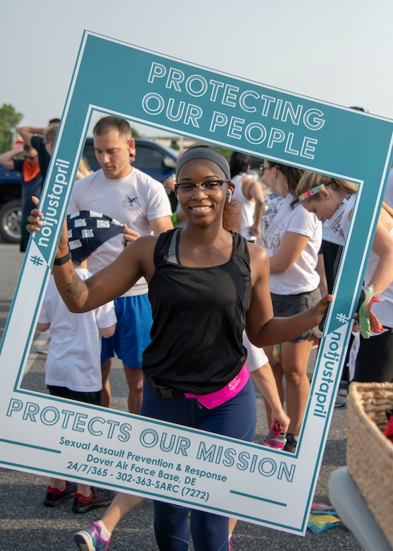 """A run participant, poses for a photo at the 2019 Sexual Assault Prevention and Response Color Run June 5, 2019, at Dover Air Force Base, Del. The purpose of the run was to raise awareness of sexual assault and to reinforce the motto, """"protecting our people protects our mission."""" (U.S. Air Force photo by Staff Sgt. Esteban Esquivel)"""