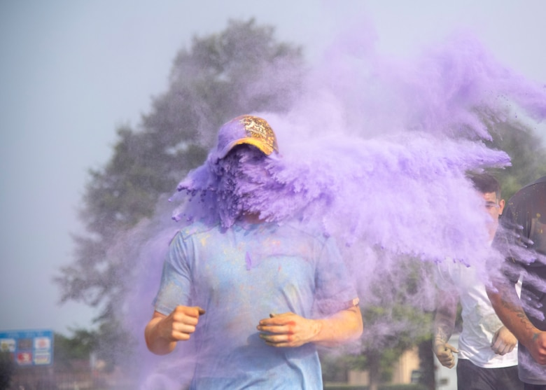 Volunteers throw purple color powder at runners during the 2019 Sexual Assault Prevention and Response Color Run June 5, 2019, at Dover Air Force Base, Del. The mixture of cornstarch, baking soda and dyes is safe and environmentally friendly. (U.S. Air Force photo by Staff Sgt. Esteban Esquivel)