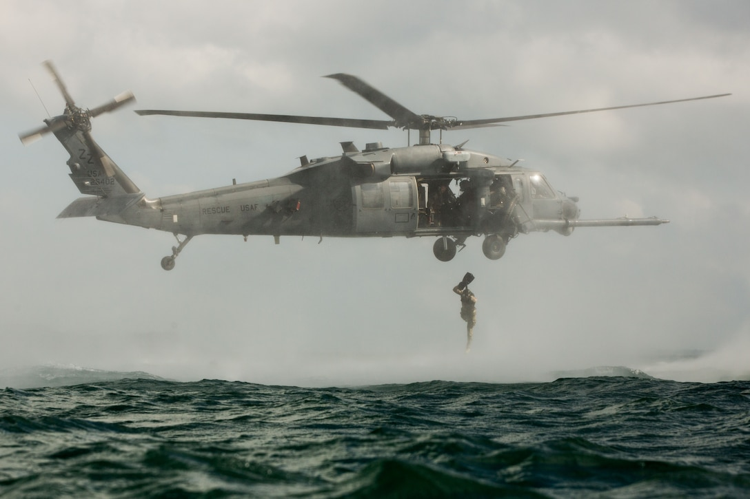 A Marine jumps from a helicopter into the ocean.