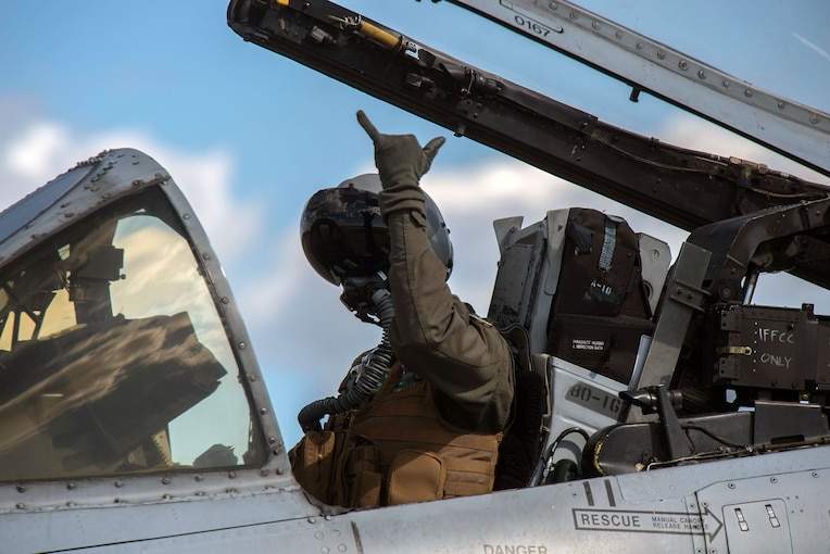 An Air Force pilot gives a hand signal while in an open cockpit.
