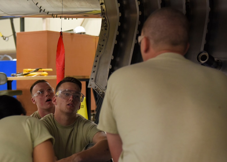 Airman 1st Class Daniel Hawkins (center), 361st Training Squadron aerospace propulsion apprentice, discusses the various engine components of a McDonnell Douglas F-15 Eagle with Staff Sgt. Matthew Hansen (right), 361st Training Squadron aerospace ground propulsion instructor, at Sheppard Air Force Base, Texas, Jun. 10, 2019. Hawkins, an ACE award recipient, received a score of 100% on all of his progress checks and block tests during his training course. Hawkins enjoys the challenges that along come with his job. (U.S. Air Force photo by Senior Airman Ilyana A. Escalona)
