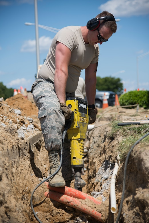 Airman 1st Class Keifer Donovan, 436th Civil Engineer Squadron pavement and equipment apprentice, uses a jackhammer to break up rocky terrain near the main gate for a French drain installation project June 3, 2019, at Dover Air Force Base, Del. With various power and gas lines buried around the dig site, the majority of digging was accomplished using a pickaxe and shovel. (U.S. Air Force photo by Airman 1st Class Jonathan Harding).