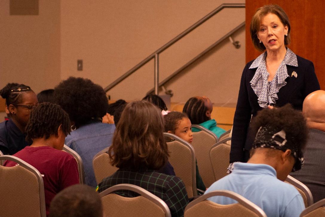 A woman speaks to children in an auditorium.