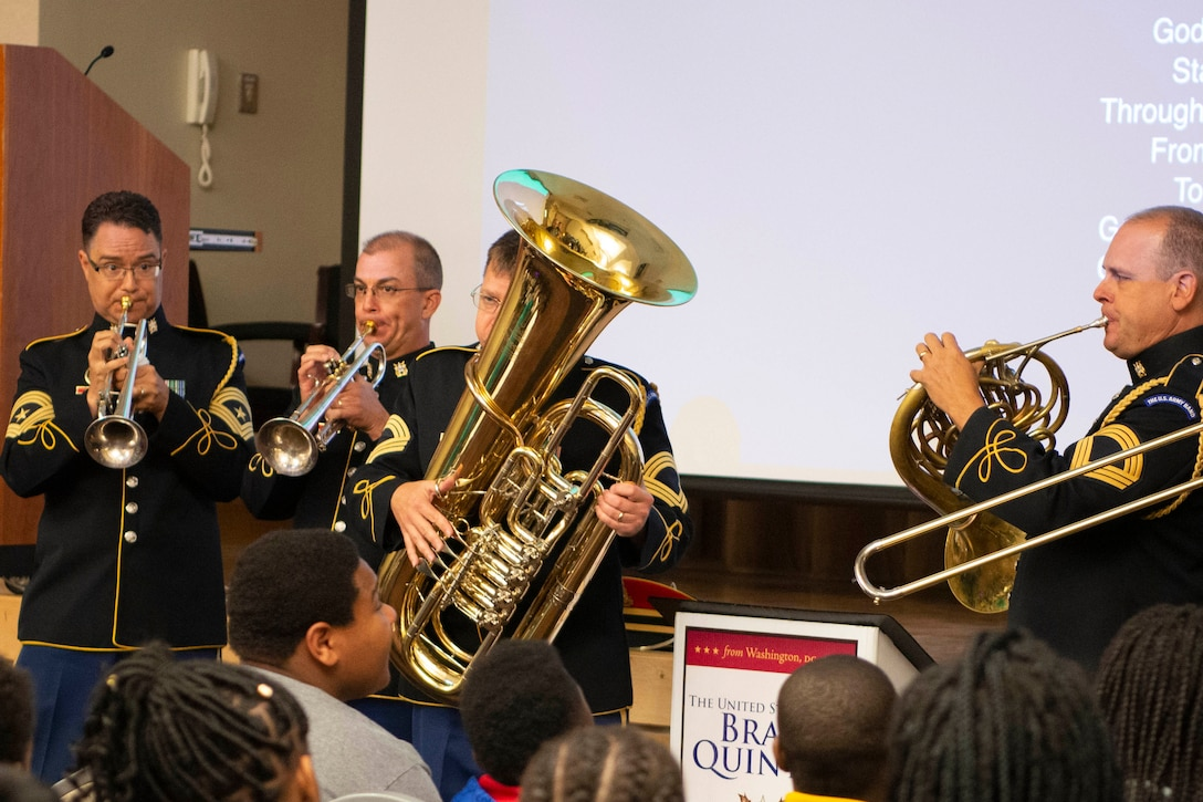 A military brass band plays for an audience of kids.