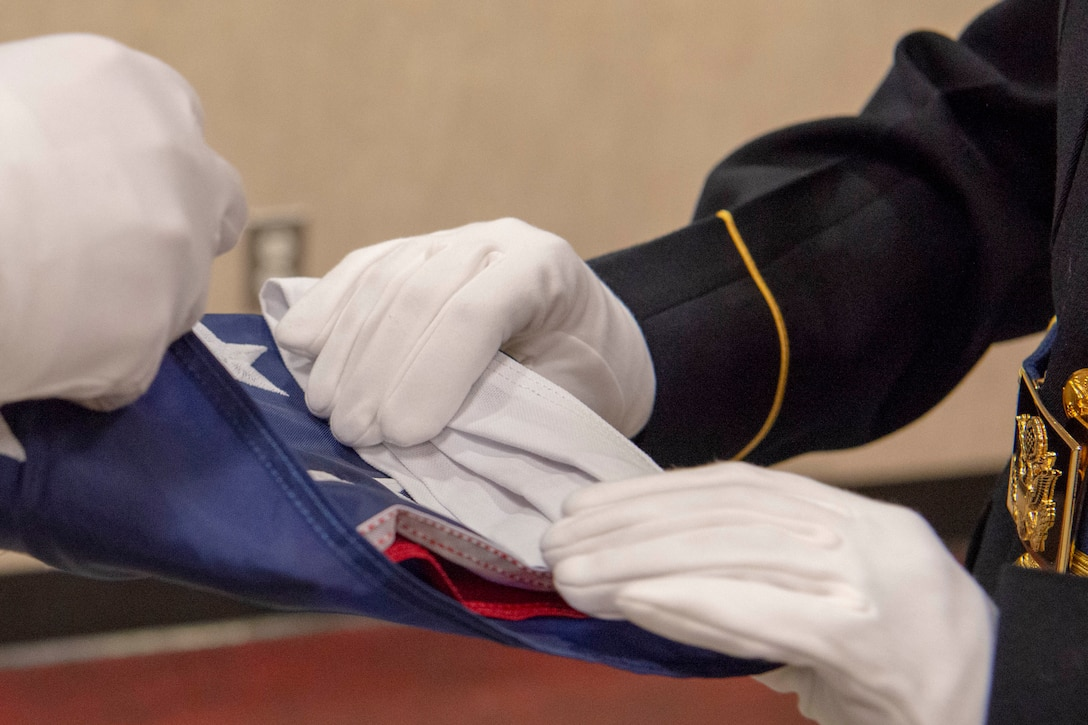 Service members wearing gloves fold an American flag.