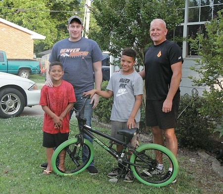Torren Jackson (center) is pictured with rescuers that helped free him from swift running water May 29, 2019 when he was swept from the road while riding his bike and trapped inside a culvert in Prague, Oklahoma. From left: Teggan Jackson, Dakota Fite, Torren Jackson and Eric Whitesel. (Courtesy photo by Sharon Lee/Prague Times Herald)