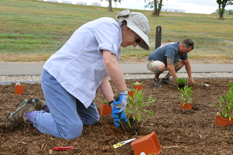 (left to right) Bee Hall and Steve Vlaming, both 75th Civil Engineering Group, plant vegetation at the new pollinator garden plot, June 6, 2019, at Hill Air Force Base, Utah. The garden will provide food and habitat for pollinator species such as hummingbirds, bees, and other insects, which are critical to maintaining diverse and healthy ecosystems. (U.S. Air Force photo by Todd Cromar)