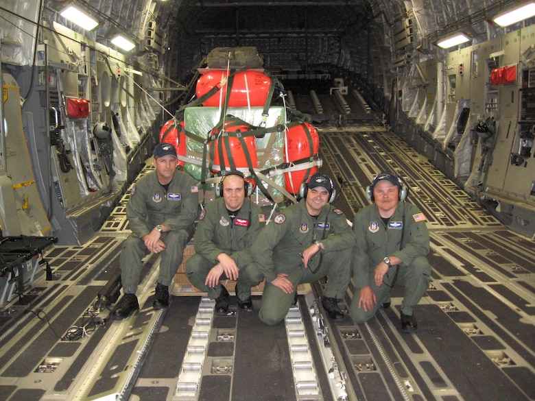 Chief Master Sgt. James Masura Jr., 313th Airlift Squadron loadmaster, and 304th Expeditionary Air Squadron loadmasters, pause for a photo with the airdrop equipment to aid a fishing vessel broken down in the Antarctic. Argos Georgia had suffered serious engine failure while heading south in the Ross Sea, leaving it without propulsion and drifting with the ice Jan. 4, 2008, according to an article released by PACAF Public Affairs. The vessel needed critical engine repair parts airdropped to them so crews could fix damaged caused by navigating the icy waters. (Courtesy photo)