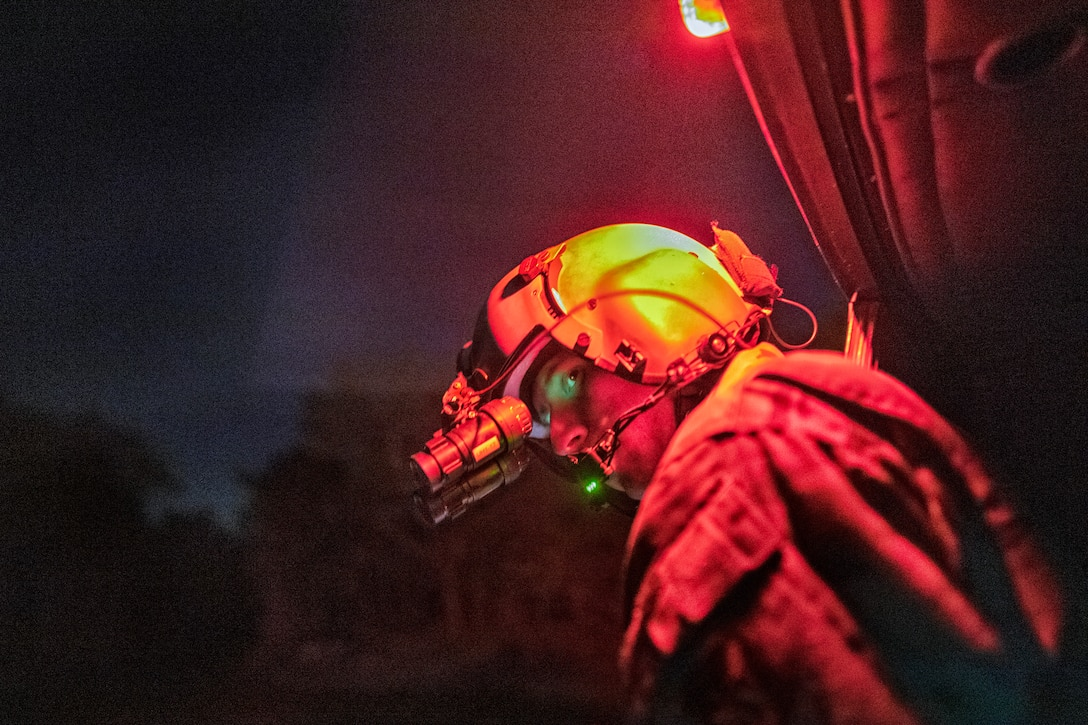 An airman wearing a helmet and goggles stands underneath a red light at night.