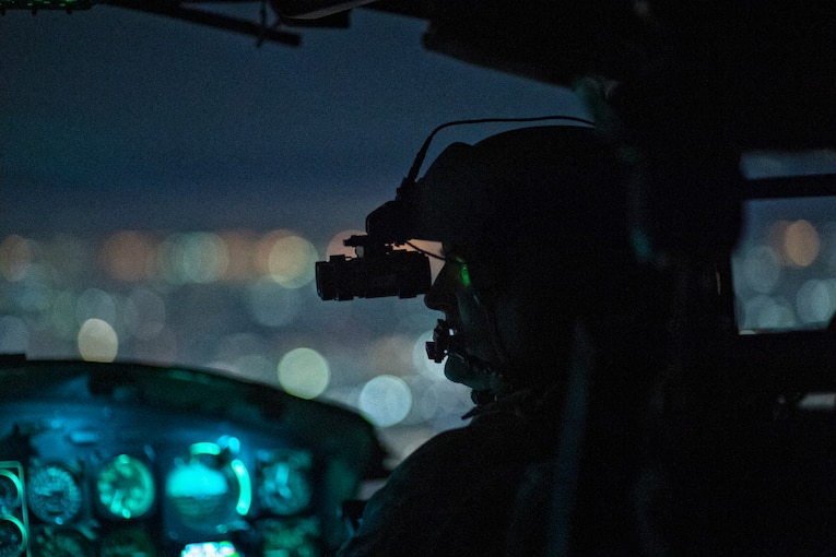 An airman sits inside of a plane wearing a helmet and goggles at night.