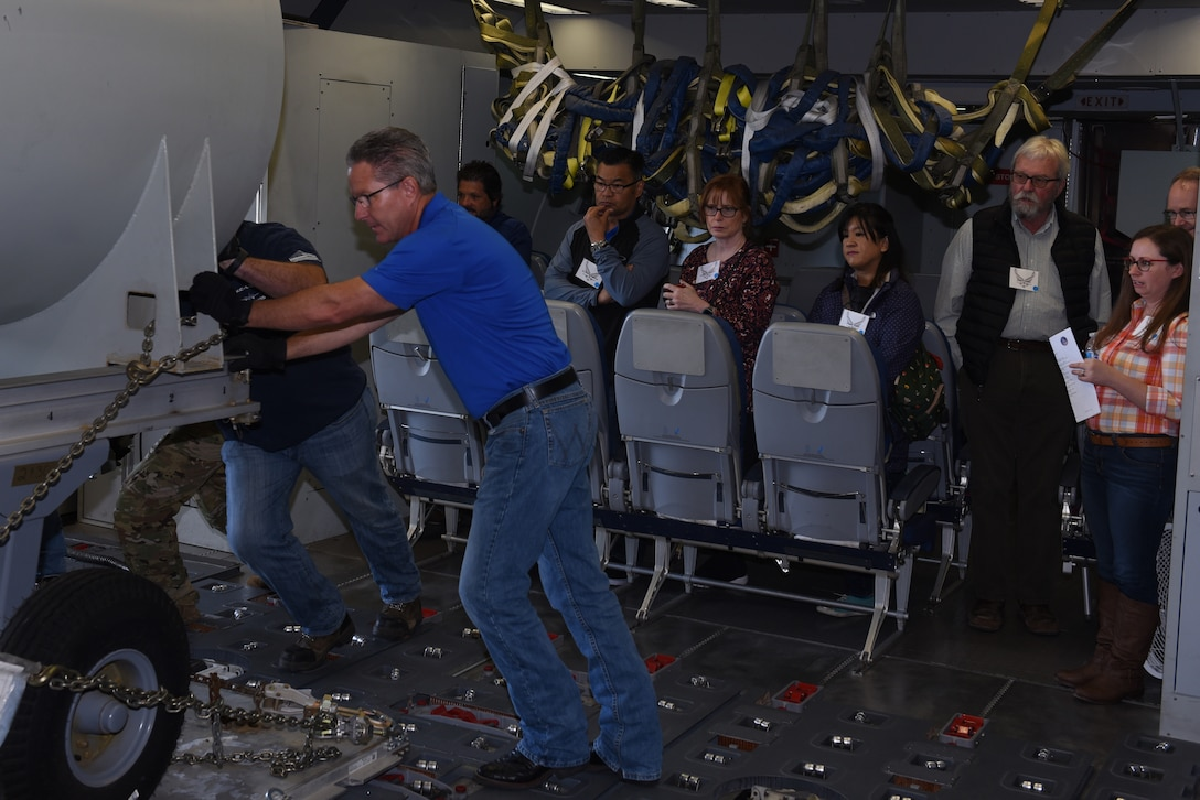 Honorary Commanders watch as Flight Safety Services Corporation members simulate loading cargo on a KC-10 Extender June 7, 2019, at Travis Air Force Base, California. The purpose of the Travis' Honorary Commander Program is to promote relationships between base senior leadership and civilian partners, foster civic appreciation of the Air Force mission and its Airmen, maximize opportunities to share the Air Force story with new stewards and to communicate mutual interest, challenges and concerns that senior leaders and civilian stakeholders have in common. (U.S. Air Force photo by Airman 1st Class Cameron Otte)