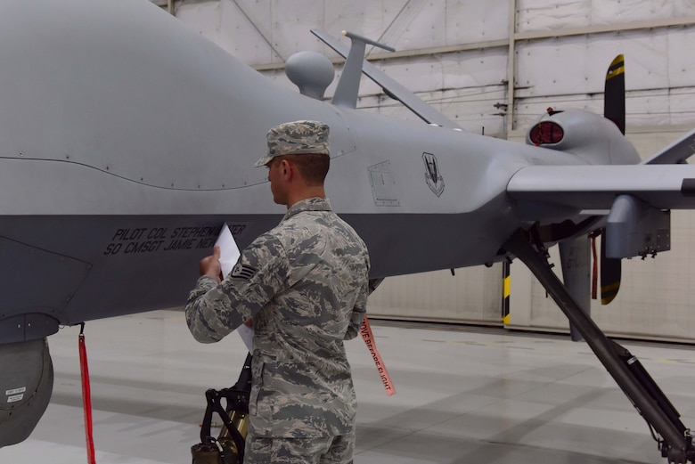 Staff Sgt. Justin, 432nd Aircraft Maintenance Squadron, unveils the name of the incoming 432nd Wing/432nd Air Expeditionary Wing commander on an MQ-9 Reaper during the 432nd WG change of command ceremony at Creech Air Force Base, Nevada, June 7, 2019. During the event, Col. Stephen Jones assumed command of the award-winning Remotely Piloted Aircraft wing from Col. Julian Cheater. (U.S. Air Force photo by Airman 1st Class Haley Stevens)