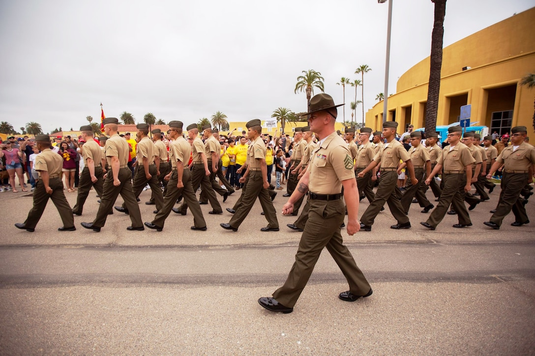A drill sergeant marches alongside several lines of new Marines.