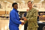 Air Force 2nd lt. Charmaine Clark of Robbins AFB, Ga. is presented All-Tournament Team honors by Navy Capt. David Yoder, Commander of Naval Station Mayport, Fla. Elite U.S. military basketball players from around the world compete for dominance at Naval Station Mayport during the 2019 Armed Forces Men's and Women's Basketball Championship. Army, Marine Corps, Navy (with Coast Guard) and Air Force teams square off at the annual event which features double round-robin action, followed by championship and consolation games to crown the best players in the military. (U.S. Navy photo by Mass Communication Specialist 1st Class Gulianna Dunn/RELEASED)