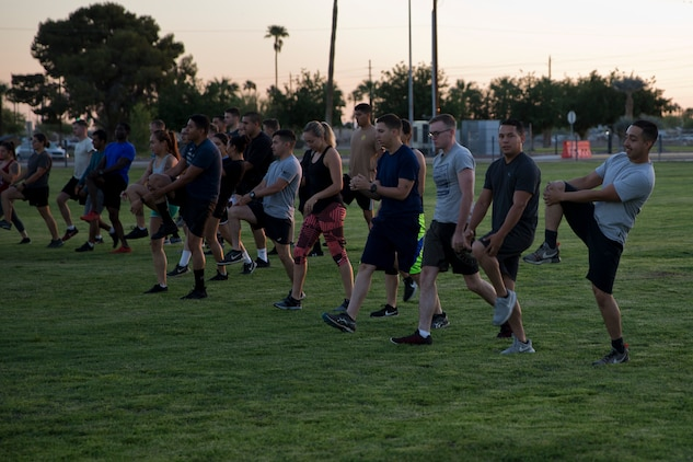 U.S. Marines and Sailors Stationed at Marine Corps Air Station (MCAS) Yuma conduct warm up drills during High Intensity Tactical Training (HITT) on The Lawn at the parade deck on MCAS Yuma Ariz., April 26, 2019. HITT on the Lawn is a physical training event that is open to anyone with base access and provides them with a physical training opportunity. (U.S. Marine Corps photo by Lance Cpl. Joel Soriano)
