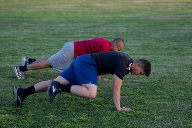 """U.S. Marines Stationed at Marine Corps Air Station (MCAS) Yuma conduct """"mountain climbers"""" during High Intensity Tactical Training (HITT) on The Lawn on the parade deck at MCAS Yuma Ariz., April 26, 2019. HITT on the Lawn is a physical training event that is open to anyone with base access and provides them with a physical training opportunity. (U.S. Marine Corps photo by Lance Cpl. Joel Soriano)"""