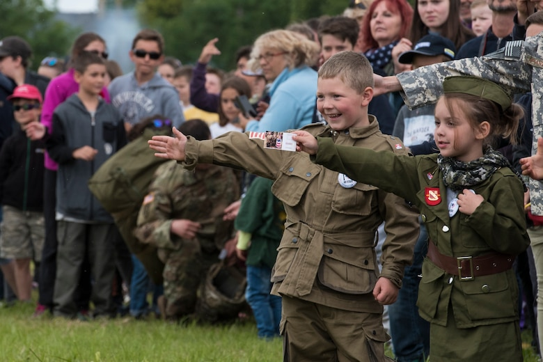 """A French boy, dressed in a mock WWII-era uniform displaying the American flag, Canadian flag and an illustrated pin stating """"I heart our veterans,"""" extends his arm waiting to high five one of the many U.S. static-line paratroopers walking by during the D-Day 75 Commemorative Airborne Operation outside of Sainte-Mère-Église, France, June 9, 2019. Next to him, a French girl, extends her hand to give the paratroopers a token of gratitude which says """"Thank You,"""" in four different languages. Thousands of spectators showed up for the multinational commemorative events to witness an airshow and 900 paratroopers descend from the skies into the Iron Mike drop-zone, commemorating D-Day, 75 years ago. (U.S. Air Force photo by Senior Airman Kristof J. Rixmann)"""