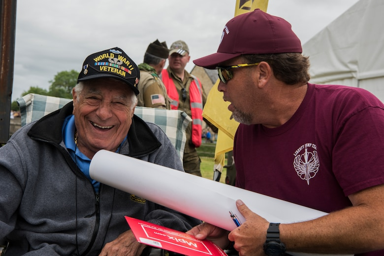 """U.S. Army World War II and D-Day veteran, Vincent Speranza, 501st Parachute Infantry Regiment, 101st Airborne Division paratrooper smiles mid-conversation during the D-Day 75 Commemorative Airborne Operation outside Sainte-Mère-Église, France, June 9, 2019. Speranza fought in the Battle of the Bulge between 1944 and 1945, a battle that would result in the highest casualties of any operation during WWII. Speranza believes in the importance of sharing his story, his piece of history, with others because as he says, and Winston Churchill has similarly said, """"Those who are not willing to learn history are doomed to repeat it."""" (U.S. Air Force photo by Senior Airman Kristof J. Rixmann)"""