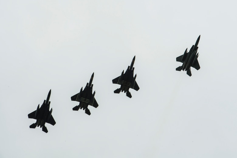 Four F-15E Strikes Eagles, assigned to the 48th Fighter Squadron, Royal Air Force Lakenheath, England,conduct a fighter escort for 23 aircraft dropping personnel into Iron Mike Drop Zone, outside of Saint-Mere-Eglise, France June 9, 2019. The F-15s were painted in honor of their predecessor aircraft, the P-47s Thunderbolts from World War II. (U.S. Air Force photo by Senior Airman Devin M. Rumbaugh)
