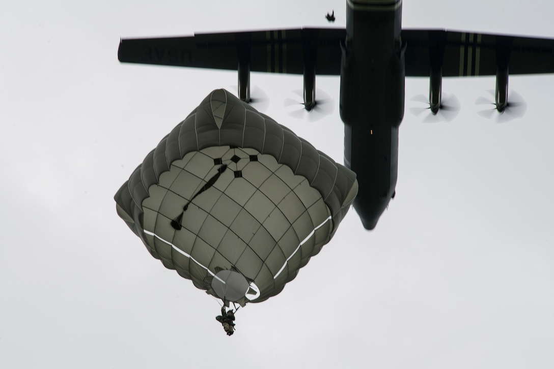 A static-line paratrooper prepares to land as a U.S. Air Force C-130J Super Hercules, assigned to the 37th Airlift Squadron, Ramstein Air Base, Germany, passed overhead during the D-Day Commemorative Airborne Operation over Iron Mike Drop Zone, outside Saint-Mere-Eglise, France June 9, 2019. Approximately 23 aircraft dropped over one thousand personnel in honor of the airborne operation held on June 6, 1944. (U.S. Air Force photo by Senior Airman Devin M. Rumbaugh)