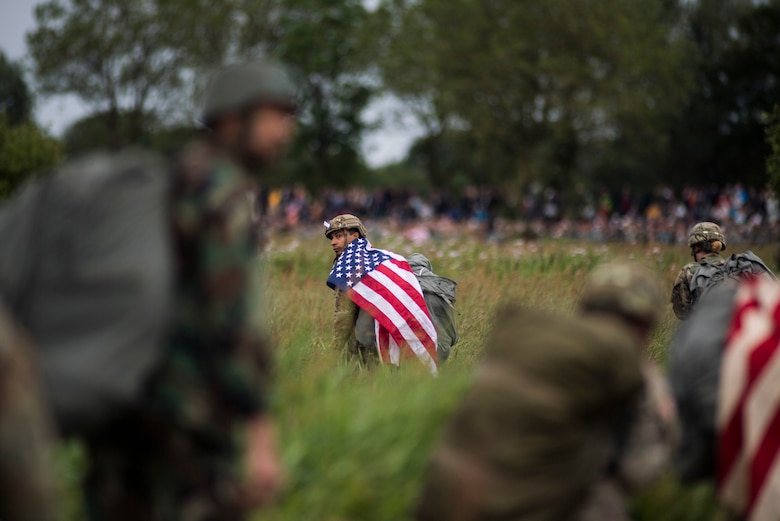 A U.S. paratrooper walks with a U.S. flag on his shoulders after conducting a static-line jump into Iron Mike Drop Zone outside of Saint-Mere-Eglise, France June 9, 2019. Paratroopers conducted the largest airdrop since Operation Neptune June 6, 1944. (U.S. Air Force photo by Senior Airman Devin M. Rumbaugh)
