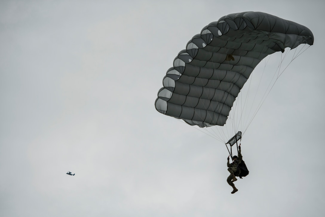 A military-free-fall paratrooper lands as a United States Air Force CV-22 Osprey, assigned to the 352nd Special Operations Wing flies above the Iron Mike Drop Zone outside of Saint-Mere-Eglise, France June 9, 2019. Iron Mike Drop Zone is a historic location to Operation Overlord. (U.S. Air Force photo by Senior Airman Devin M. Rumbaugh)