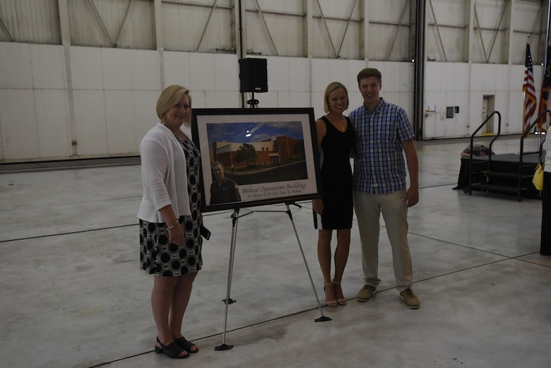 The family of U.S. Air Force Lt. Col. Joseph Mikeal pose next to a commemorative photo created for the 145th Airlift Wing building dedication ceremony at the North Carolina Air National Guard Base, Charlotte Douglas International Airport, June 9, 2019. Lt. Col. Mikeal was a member of the MAFFS 7 crew who passed away in an aircraft accident in 2012, the 145th Airlift Wing honored his and the other crew members sacrifice by naming four buildings across the wing after each one.