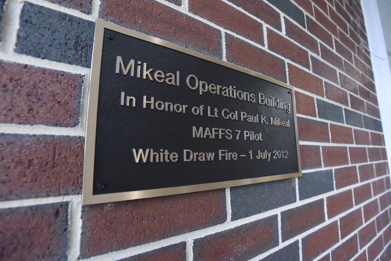 A plaque is displayed dedicating the 145th Airlift Wing C-17 operations building to U.S. Air Force Lt Col. Joseph Mikeal, a MAFFS 7 crew member, at the North Carolina Air National Guard Base, Charlotte Douglas International Airport, June 9, 2019. Lt. Col. Mikeal tragically lost his life alongside 3 other C-130 crew members in an aircraft accident in 2012, the 145th Airlift Wing honored his and the other crew members sacrifice by naming four buildings across the wing after each one.