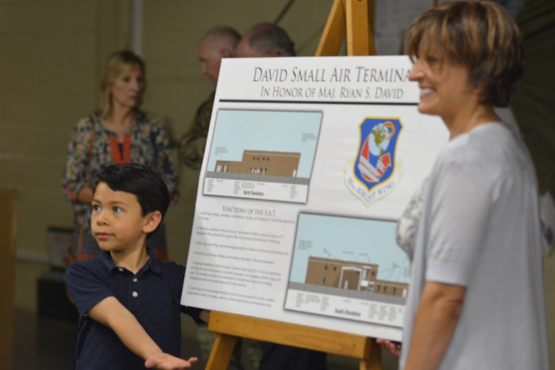 The wife and son of U.S. Air Force Maj. Ryan David show off a display made to explain the function of a Small Air Terminal, following a building dedication ceremony at the North Carolina Air National Guard Base, Charlotte Douglas International Airport, June 9, 2019. The 145th Airlift Wing dedicated four buildings across the base to the fallen members of the MAFFS aircrew, including Maj. David, who passed away in 2012 following an accident while fighting a wild fire in South Dakota.