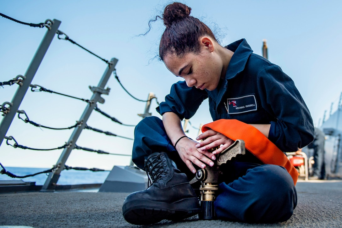 A sailor connects a fire hose while sitting cross-legged on the deck of a ship.