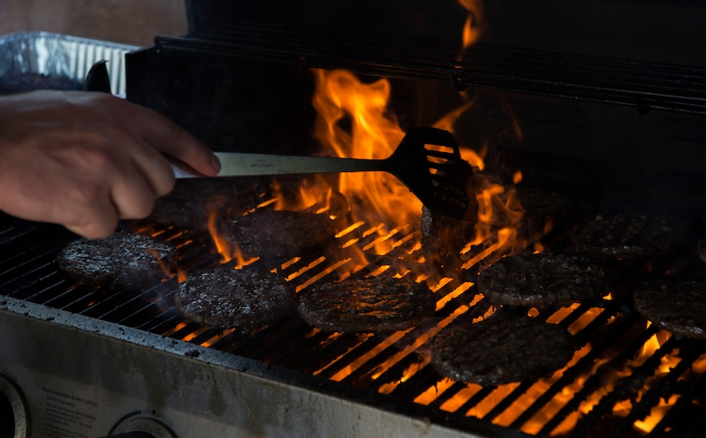 An Airman grills hamburger patties during the Chiefs Group barbecue at Schriever Air Force Base, Colorado, July 12, 2018. Both medium and large party packs come with a grill. (U.S. Air Force photo by Staff Sgt. Arielle Vasquez)