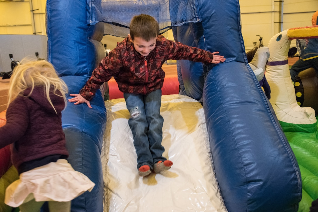 Children play in a bounce house at the Annual Children's Holiday Festival Winter Extravaganza at the indoor running track at Schriever Air Force Base, Colorado, Dec. 1, 2018. The bounce house is one of the options available in the large party pack, it is also available to add to a customized pack. (U.S. Air Force photo by 2nd Lt. Idalí Beltré Acevedo)