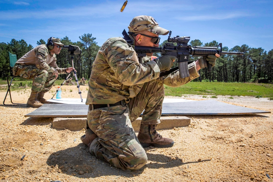 A soldier watches through a scope as a foreign soldier fires a carbine.