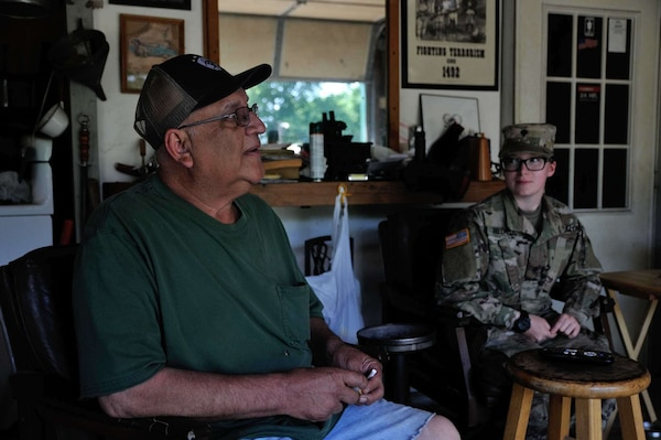 Sand Springs, Oklahoma, resident Bob Casebold sits in his garage with Spc. Kailey Bellville, a unit supply specialist in Headquarters Company, 1st Battalion, 279th Infantry Regiment, 45th Infantry Brigade Combat Team, Oklahoma Army National Guard, after she helped lay sandbags around trees at his Sand Springs home May 30, 2019.