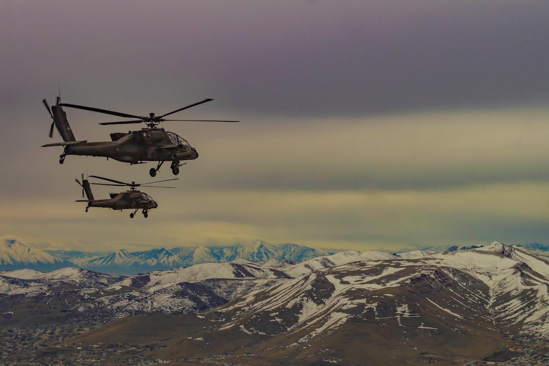 Two helicopters fly over snowcapped mountains.