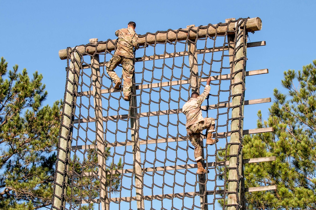Two soldiers, shown from behind, navigate a wide rope ladder against a blue sky.