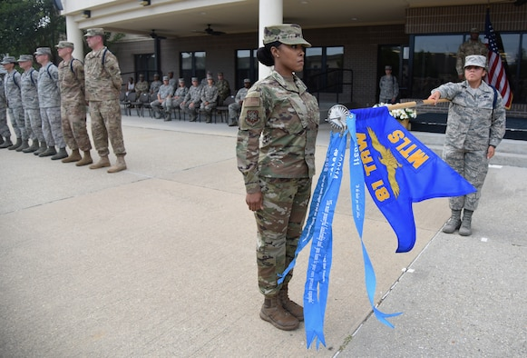 U.S. Air Force Master Sgt. Ladwidia Castro, 81st Training Support Squadron military training leader course student, adds a ribbon to a streamer to the 81st Training Wing Military Training Leadership schoolhouse flag during a MTL course graduation ceremony at the Levitow Training Support Facility on Keesler Air Force Base, Mississippi, May 30, 2019. The MTL course is responsible for training approximately 120 MTLs per year. Those MTLs are then responsible for training approximately 30,000 Airmen in 49 different locations that fall under Air Education and Training Command. (U.S. Air Force photo by Kemberly Groue)