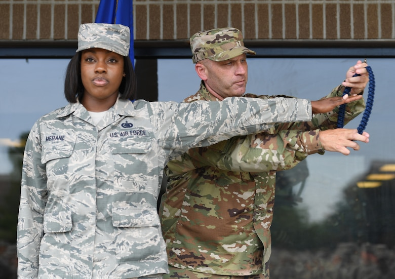 U.S. Air Force Chief Master Sgt. Anthony Fisher, 81st Training Group superintendent, presents a blue rope to Staff Sgt. Allison Mebane, 81st Training Support Squadron military training leader course student, during a MTL course graduation ceremony at the Levitow Training Support Facility on Keesler Air Force Base, Mississippi, May 30, 2019. The MTL course is responsible for training approximately 120 MTLs per year. Those MTLs are then responsible for training approximately 30,000 Airmen in 49 different locations that fall under Air Education and Training Command. (U.S. Air Force photo by Kemberly Groue)