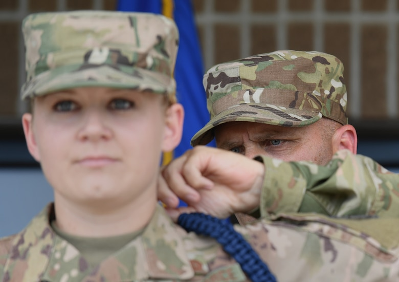 U.S. Air Force Chief Master Sgt. Anthony Fisher, 81st Training Group superintendent, presents a blue rope to Staff Sgt. Ashley Herring, 81st Training Support Squadron military training leader course student, during a MTL course graduation ceremony at the Levitow Training Support Facility on Keesler Air Force Base, Mississippi, May 30, 2019. The MTL course is responsible for training approximately 120 MTLs per year. Those MTLs are then responsible for training approximately 30,000 Airmen in 49 different locations that fall under Air Education and Training Command. (U.S. Air Force photo by Kemberly Groue)