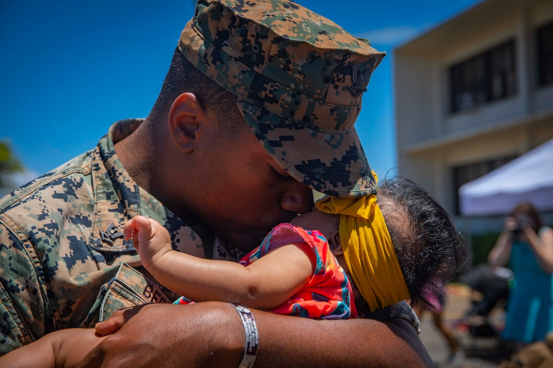 A sailor in a camouflage uniform and cover kisses and holds a baby in his arms.