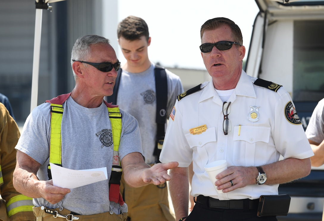 Rusty Bell, 81st Infrastructure Division firefighter, and Gary Pierson, 81st ID deputy fire chief, discuss approaching procedures during an aircraft rescue fire fighting training on Keesler Air Force Base, Mississippi, June 4, 2019. The joint agency training allowed the Keesler Fire Department, Gulfport Combat Readiness Training Center Fire Department, Stennis Airport Fire Department and the U.S. Naval Air Station Pensacola Gulf Coast Fire Rescue to meet the semi-annual training requirement to practice aircraft rescue and live fire training evolutions. (U.S. Air Force photo by Kemberly Groue)