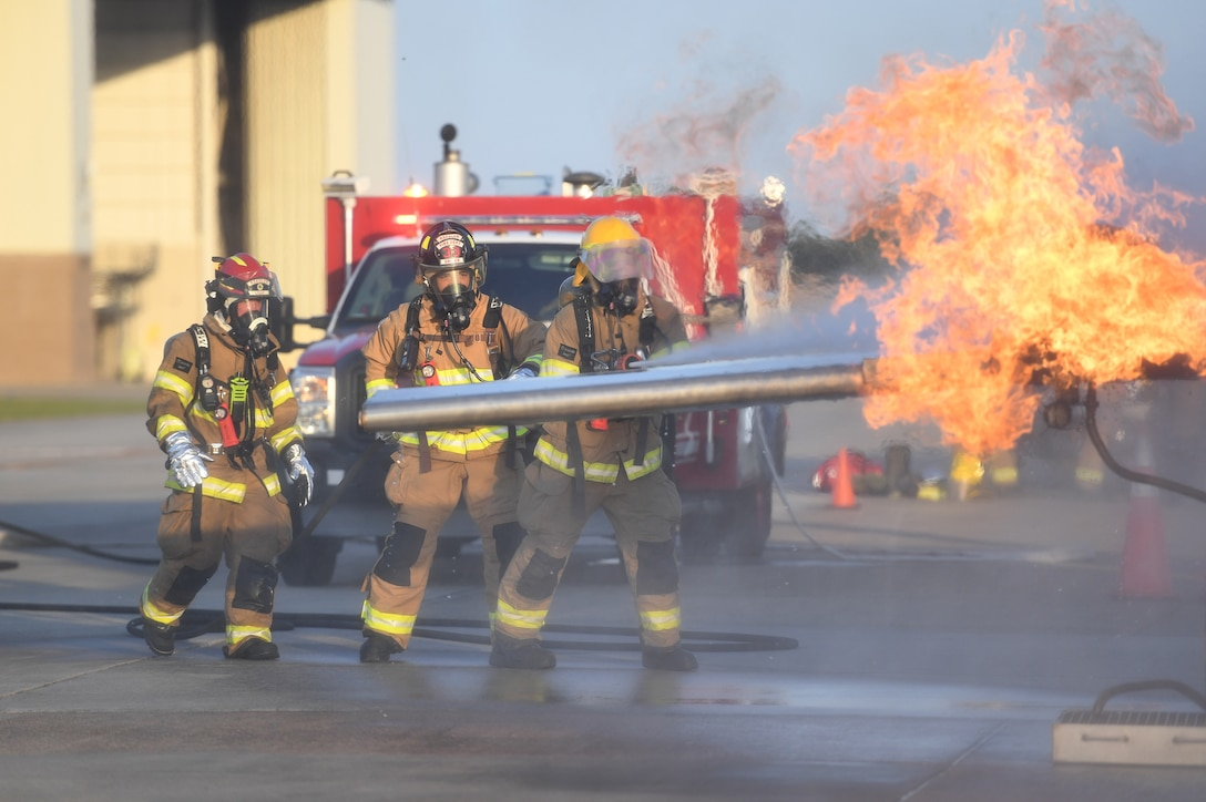 Keesler firefighters use a hand-held hose to extinguish a fire on a mock C-123 training device during an aircraft rescue fire fighting training on Keesler Air Force Base, Mississippi, June 4, 2019. The joint agency training allowed the Keesler Fire Department, Gulfport Combat Readiness Training Center Fire Department, Stennis Airport Fire Department and the U.S. Naval Air Station Pensacola Gulf Coast Fire Rescue to meet the semi-annual training requirement to practice aircraft rescue and live fire training evolutions. (U.S. Air Force photo by Kemberly Groue)