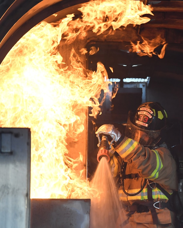A Keesler firefighter uses a hand-held hose to extinguish a fire inside a mock C-123 training device during an aircraft rescue fire fighting training on Keesler Air Force Base, Mississippi, June 4, 2019. The joint agency training allowed the Keesler Fire Department, Gulfport Combat Readiness Training Center Fire Department, Stennis Airport Fire Department and the U.S. Naval Air Station Pensacola Gulf Coast Fire Rescue to meet the semi-annual training requirement to practice aircraft rescue and live fire training evolutions. (U.S. Air Force photo by Kemberly Groue)