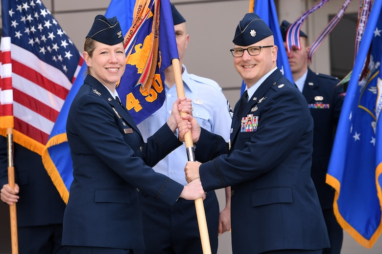 Col. Laurel Walsh, 50th Operations Group commander, passes the guidon to Lt. Col. Timothy Ryan, incoming 4th Space Operations Squadron commander, during a change of command ceremony at Schriever Air Force Base, Colorado, June 10, 2019. The 4th SOPS operates the Air Force's protected and wideband military satellite communication    systems providing warfighters global, secure, survivable, strategic and tactical communication during peacetime and throughout the full spectrum of conflict. The squadron also operates three mobile constellation control stations at various locations in conjunction with host partners. (U.S. Air Force photo by Dennis Rogers)