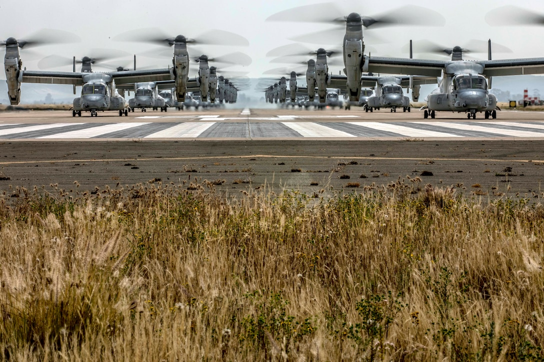 The rotors of two lines of Ospreys spin as the aircraft sit on a runway.