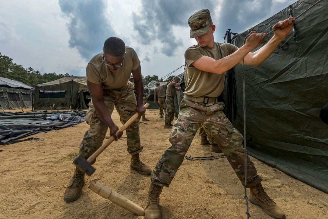 One soldier hammers a tent stake into the ground while another holds up part of the tent.